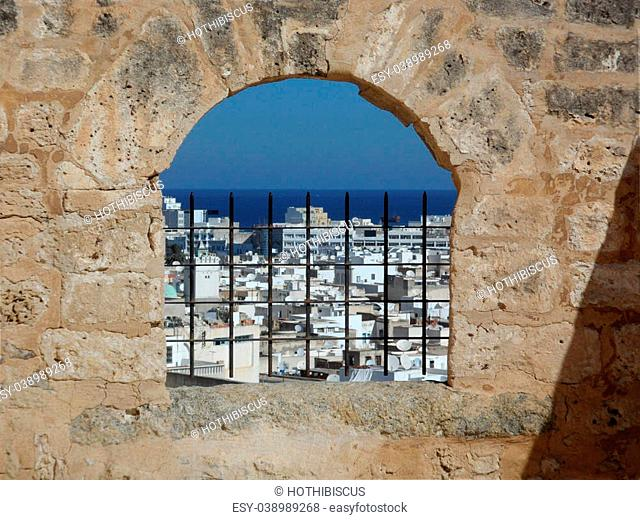 View overlooking the rooftops of buildings in old Sousse town, through an arch window in the Kasbah stone wall of the Medina, Tunisia