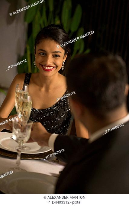 Singapore, Man and woman drinking champagne at formal dinner