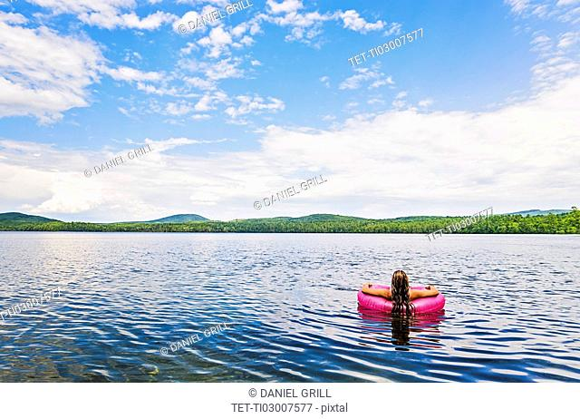 Young woman relaxing on lake in pool raft