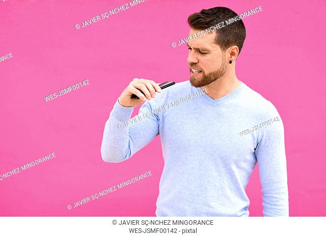 Young man recording a voice note with a smartphone, pink background