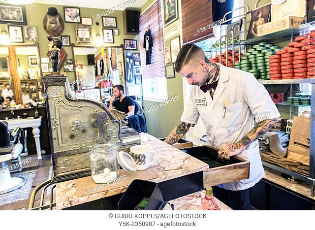Rotterdam, Netherlands. Barber store Schorem. Barber finishing a financial transaction at the retro cash register