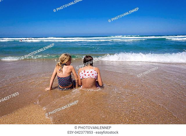Sisters girls sitting beach sands ocean wave shorebreak wash holidays