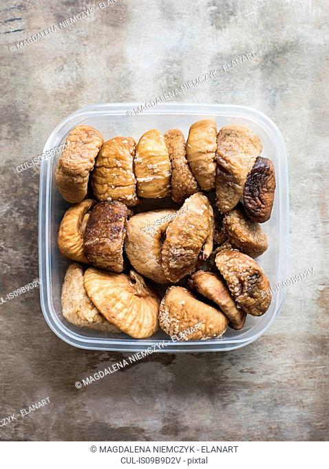 Dried figs in plastic container, close-up