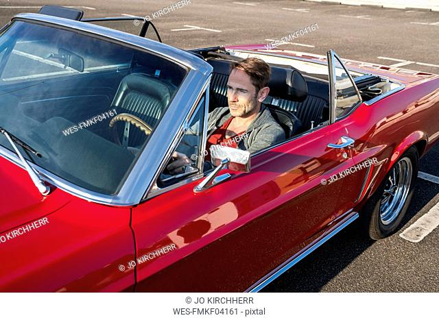 Mature man sitting in his red sports car
