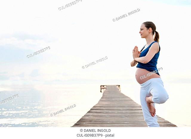 Pregnant woman on pier in yoga position, Majorca, Spain