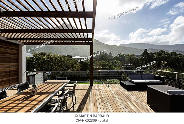 Sunny modern luxury home showcase exterior with wooden deck and mountain view