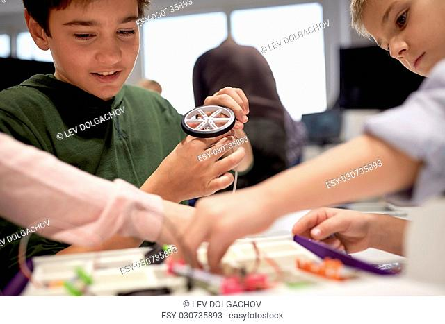 education, children, technology, science and people concept - group of kids with building kit at robotics school lesson