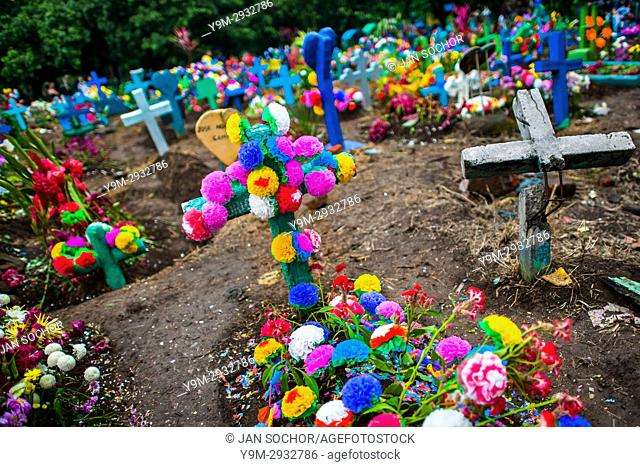 Graves decorated with colorful flowers, both paper and real ones, are seen during the Day of the Dead festivities at the cemetery in Izalco, El Salvador