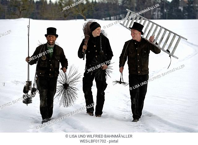 Three laughing chimney sweeps walking in snow