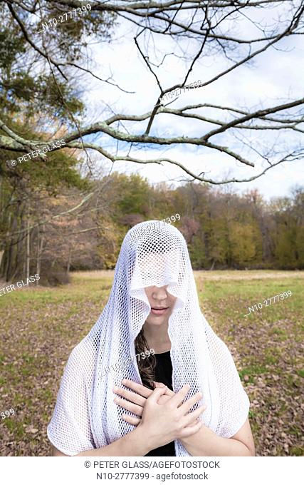 Young woman, standing in an open field, wearing a veil over her head
