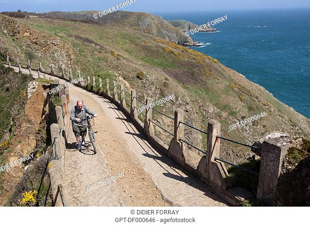 CYCLIST CROSSING THE LA COUPEE ISTHMUS, THE VERY NARROW LAND THAT LINKS THE TWO PARTS OF THE ISLAND, ISLAND OF SARK, CHANNEL ISLANDS