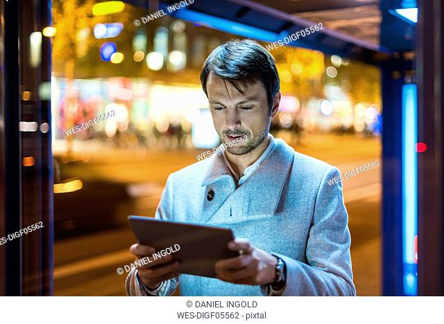 Businessman with digital tablet standing at a bus stop at night