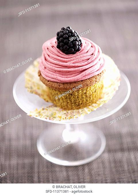 A pistachio and blackberry cupcake