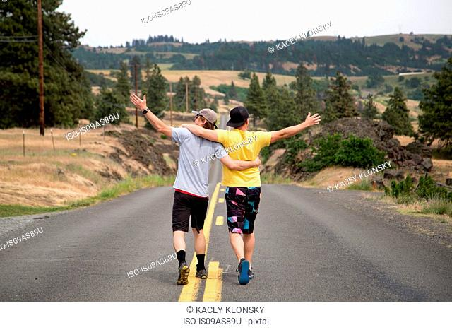 Two men walking along road together, arms raised, appreciating view, rear view