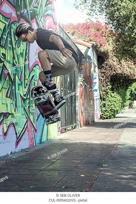 Young man doing jump on skateboard, mid air