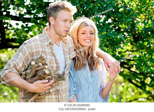 Couple gathering firewood outdoors