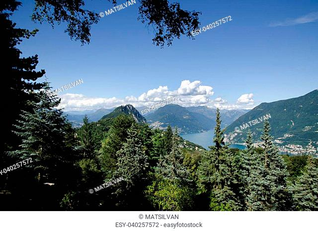 Panorama view over lugano lake with mountains and trees and blue sky with clouds in ticino switzerland