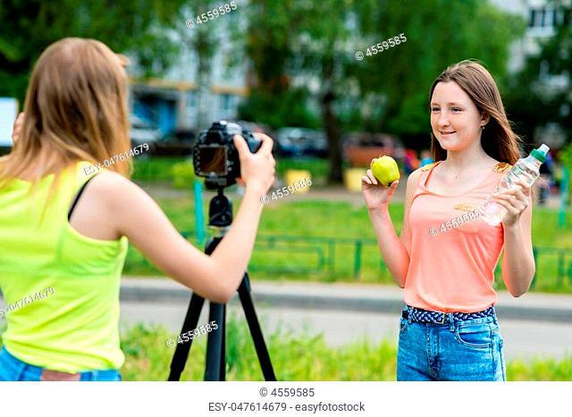 Two girls schoolgirl girlfriends. Summer nature. The concept healthy eating. Hand holds bottle water green apple. Record vlog blog subscribers