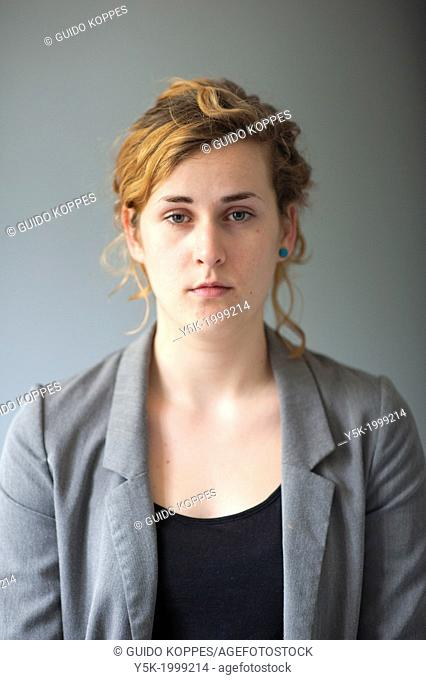 Tilburg, Netherlands. Studio-portrait of a young woman against a grey background, looking into the camera. Front view