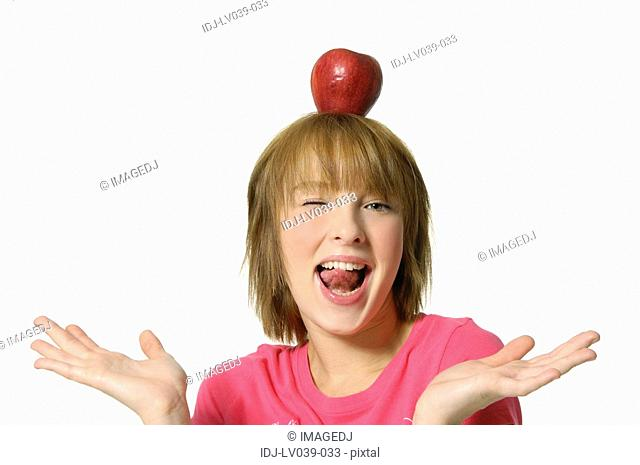 Portrait of a young woman holding an apple on her head and winking