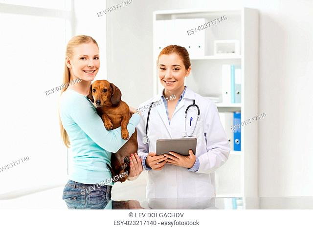 medicine, pet, health care, technology and people concept - happy woman holding dachshund dog and veterinarian doctor with tablet pc computer at vet clinic