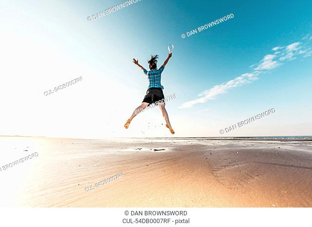 Woman jumping with light bulb on beach