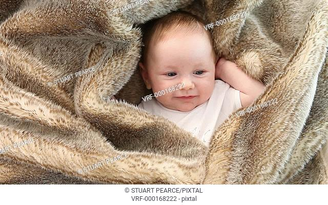 Happy baby wrapped in a fur rug