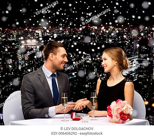 celebration, christmas, holidays and people concept - smiling couple with red gift box and ring at restaurant over snowy night city background