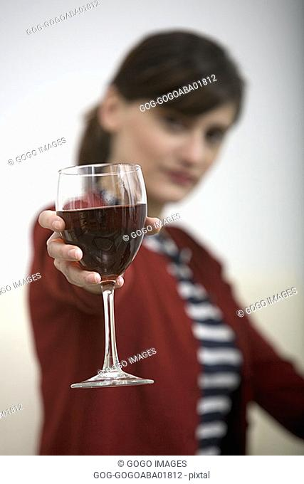 Woman holding out a glass of wine