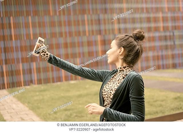 woman using smartphone, taking selfie, video conversation