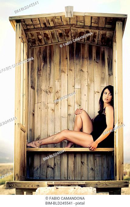 Caucasian woman sitting in cabana on beach