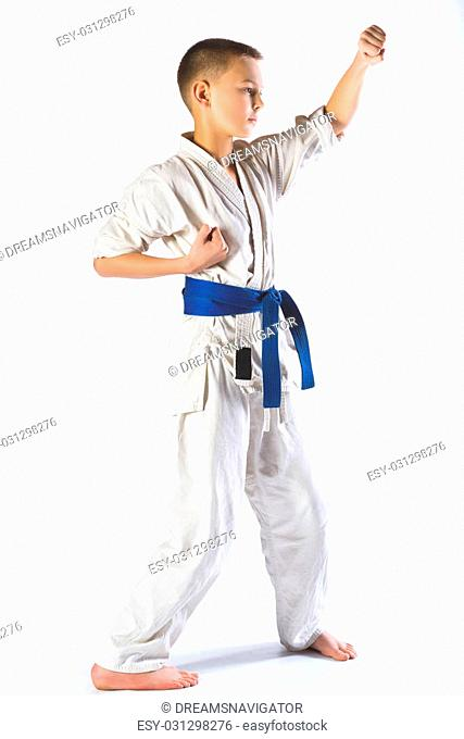 Karate boy in kimono fighting on a white background