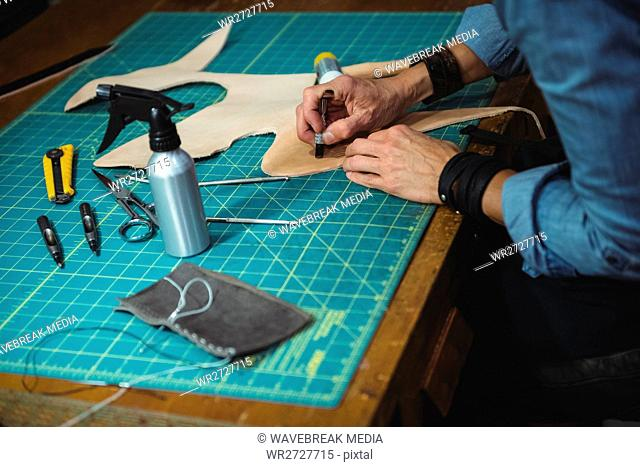 Craftswoman working on a piece of leather in workshop