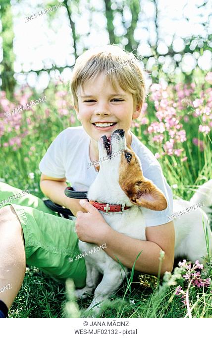 Portrait of smiling little boy sitting with his dog on meadow in the garden
