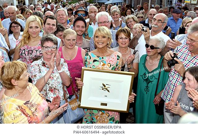 Actress Uschi Glas (C) stands surrounded by members of the public as she holds her award 'the Goldener Schlemmerente' in her hands in Wassenberg, Germany