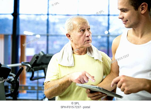 MODEL RELEASED. Trainer holding digital tablet and talking with senior man in gym