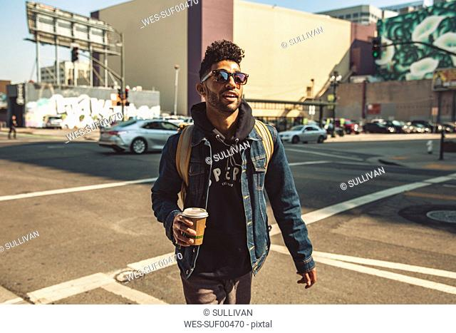 Portrait of stylish young man with coffee on the street