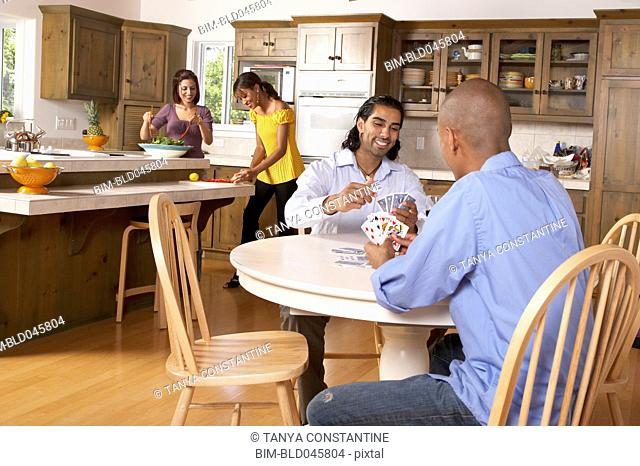 Multi-ethnic couples preparing dinner and playing cards