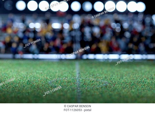The center field of a miniature soccer field, spectator figurines in background