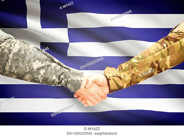 Soldiers shaking hands with flag on background - Greece