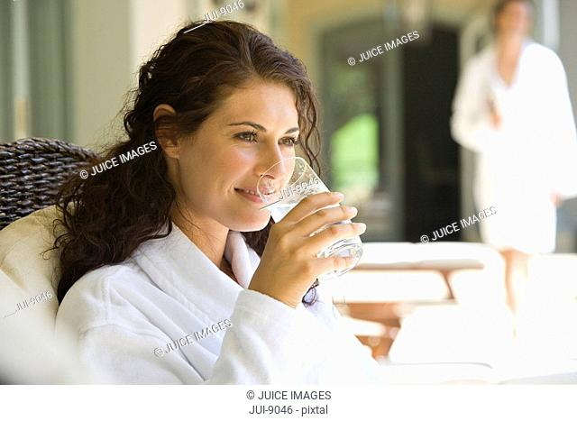 Woman wearing white robe, drinking glass of water, smiling, man standing in background