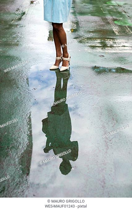 USA, New York, young african-american woman standing on street, high heels, water reflection in puddle