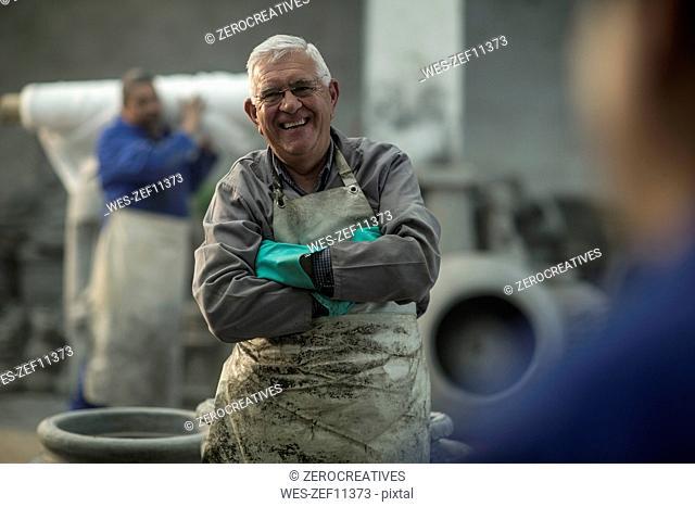 Portrait of smiling worker in industrial pot factory