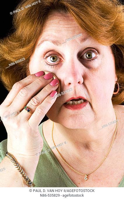 Older woman applying powder make up
