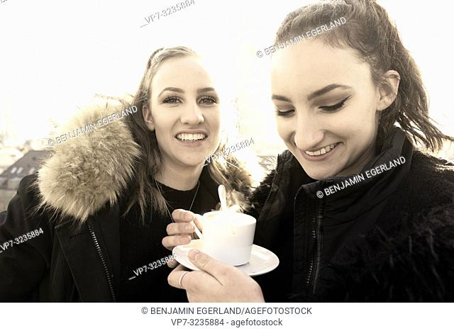 Two young sisters warm coffee cup outdoors next to Frauenkirche, Marienkirche, in city Munich, Germany