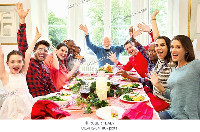 Portrait enthusiastic multi-ethnic multi-generation family waving at Christmas dinner table