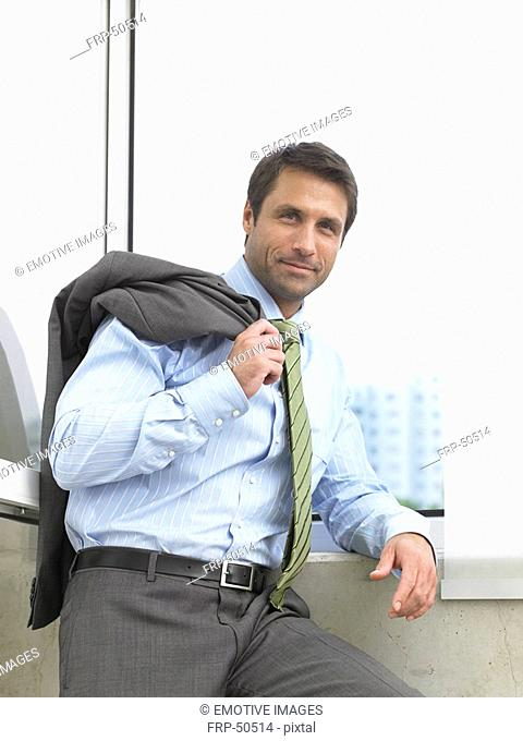 Business man with his jacket over his shoulder is standing at the window