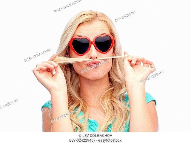 emotions, expressions, hairstyle and people concept - smiling young woman or teenage girl making mustache with strand of hair