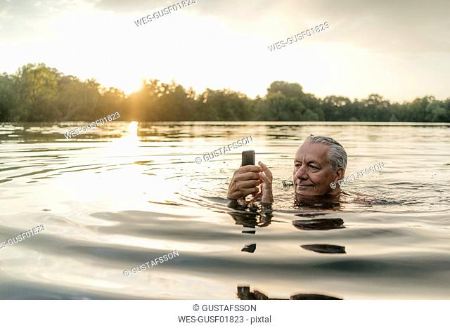 Senior man swimming in a lake at sunset using cell phone