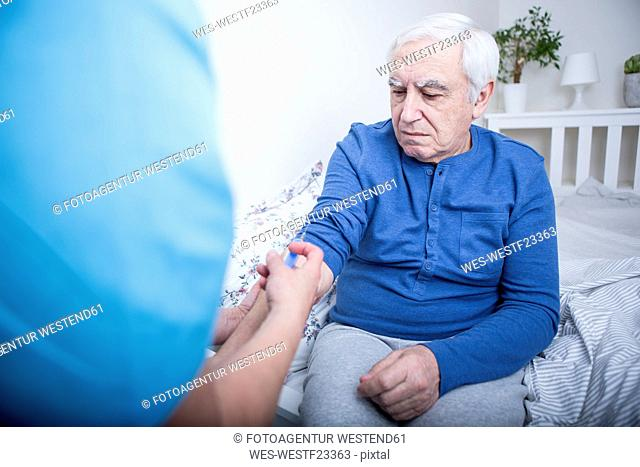 Gereatric nurse giving patient an injection